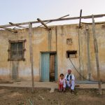 My daugher Layla sitting next to my father's oldest brother in front of the now abandoned earthen home in Gharyan