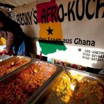 A woman sells food from Ghana at a market in Berlin. (AFP)