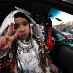A Libyan girl in traditional tribal costume flashes the V-sign for victory as families parade in their cars through the streets of Tripoli in celebration on February 16 2012, the eve of the first anniversary of the revolt against Muammar Gaddafi. (AFP)