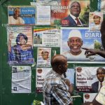 Malians look at posters displaying candidates for the upcoming presidential election. (Pic: AFP)