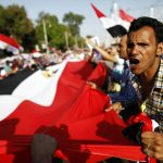 Opponents of President Morsi shout slogans while holding a giant Egyptian flag outside the presidential palace in Cairo. (AFP)
