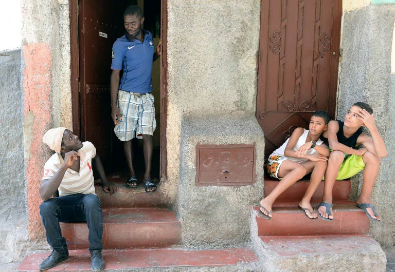 Senegalese immigrants and Moroccan children sit in front of a building where they rent flats in the Takaddum neighbourhood of Rabat. (Pic: AFP)