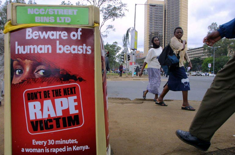 People walk past a poster bearing a message against rape on a street in Nairobi on November 24 2005. (Pic: AFP)