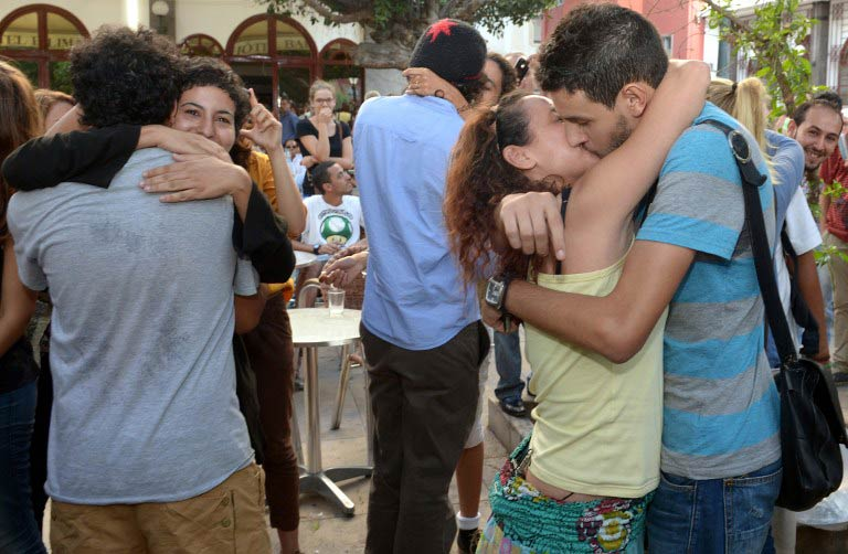 """Participants take part in a """"kiss-in"""" outside the Parliament in the Moroccan capital Rabat on October 12 2013. (Pic: AFP)"""