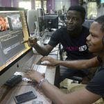 Video editors David Adeoti (L) and Jolaosho Oladimeji preview a work at the headquarters of Iroko tv in Lagos. (Pic: AFP)