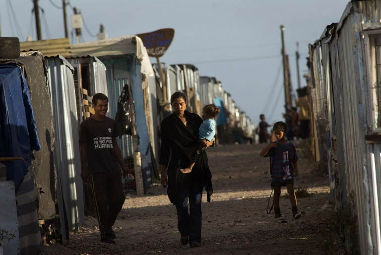 "A woman carrying a child walks down an alleyway in Blikkiesdorp (""Tin Can Town"" in Afrikaans), a settlement of corrugated iron houses about 25km east of Cape Town. (Pic: AFP)"