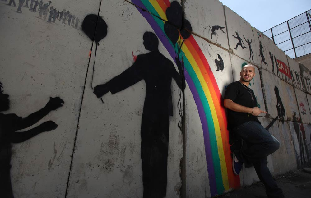Mohamed El Deeb, a 28-year-old rap and hip hop singer, poses during the making of his music video, in front of a wall with graffiti near Tahrir square in Cairo June 4 2012. (Reuters)