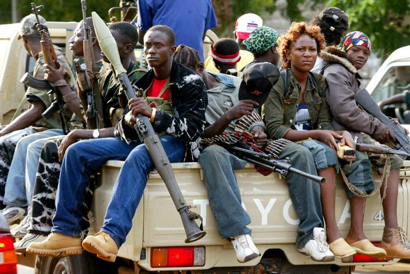 A pick-up with young soldiers loyal to then Liberian president Charles Taylor escorts Taylor's armoured SUV on a tour of the Monrovia defence line in June 2003. (Pic: AFP)