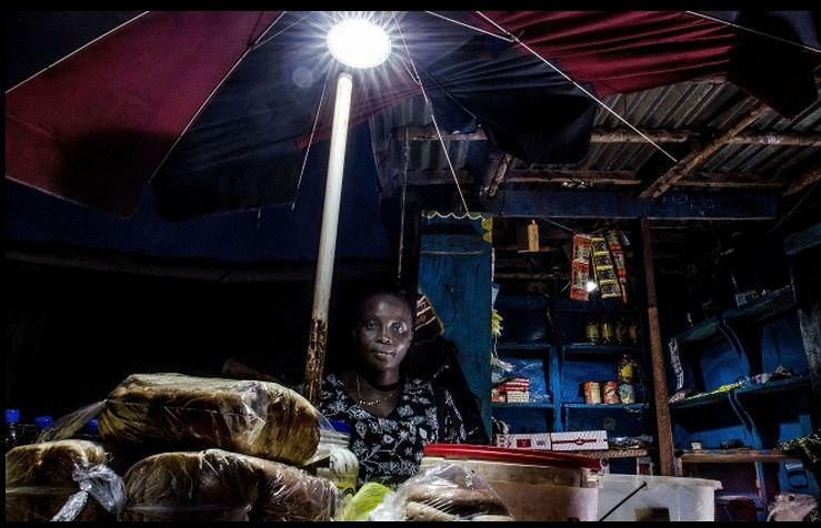 Aminatta uses an Indigo pay-as-you-go solar powered light to run her shop in Tombo village. (Pic: Tommy Trenchard/IRIN)