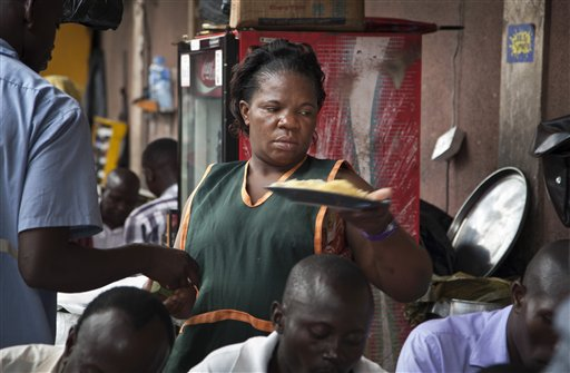 Madinah Nalukenge serves dishes to customers at her food stall, frequented by transport operators, that she owns on the edge of a bus terminal in Kampala. (Pic: AP Exchange)