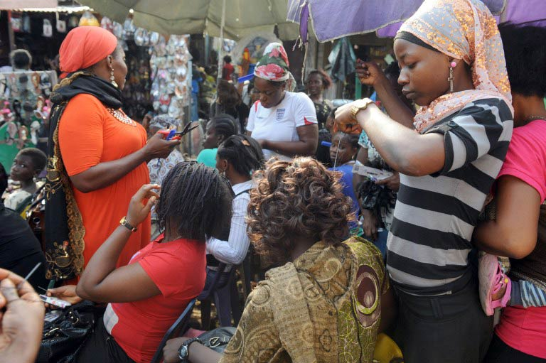 Haidressers attend to clients in Lagos, Nigeria. (Pic: AFP)