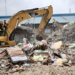 Beds used by guests are seen near an excavator at the site of the collapsed Synagogue Church of All Nations in Lagos on September 17 2014. (Pic: Reuters)