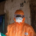 A volunteer in protective suit looks on after spraying disinfectant outside a home in Waterloo, 30km outside Freetown. (Pic: AFP)