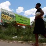 A woman walks past a billboard promoting male circumcision to combat Aids in the capital, Harare. (Pic: Reuters)