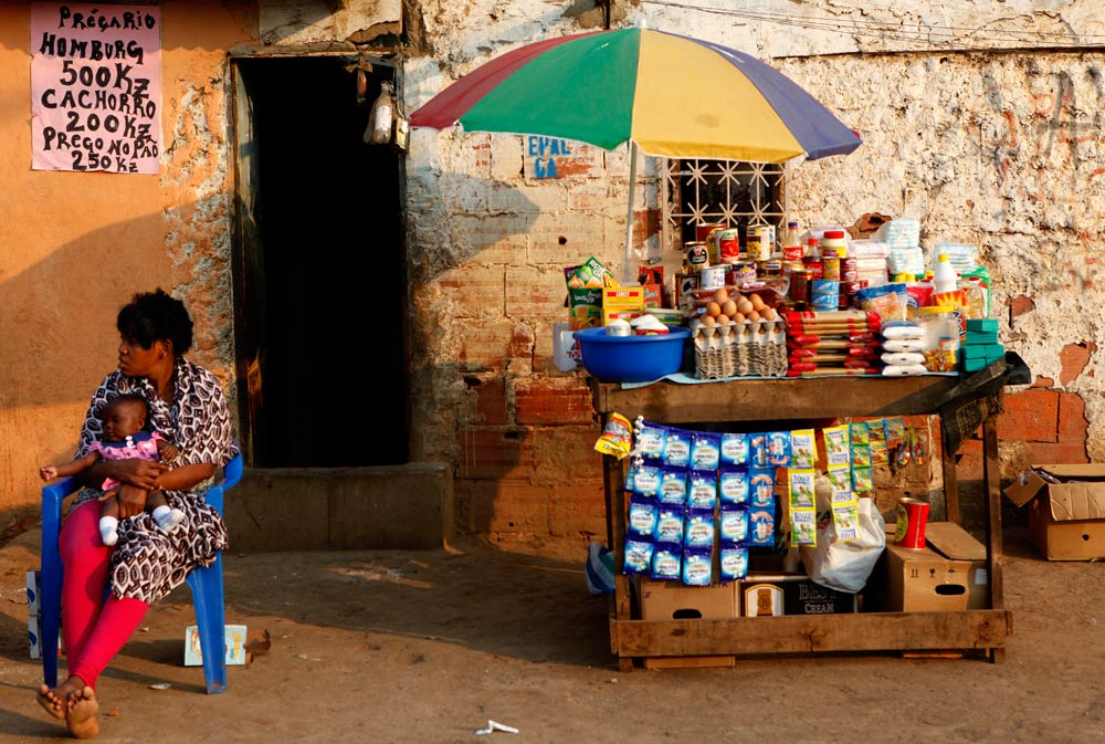 A woman and child sit in front of their stall in Sambizanga informal settlement outside the capital Luanda August on 28 2012. (Pic: Reuters)