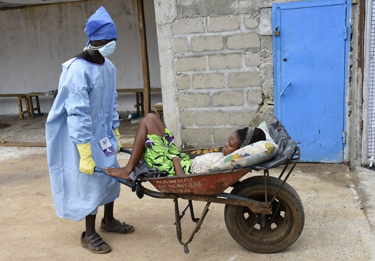 A man pushes a wheelbarrow containing a woman thought to be a victim of the Ebola virus at the Ebola treatment centre at Island hospital in Monrovia on October 2 2014. (Pic: AFP)