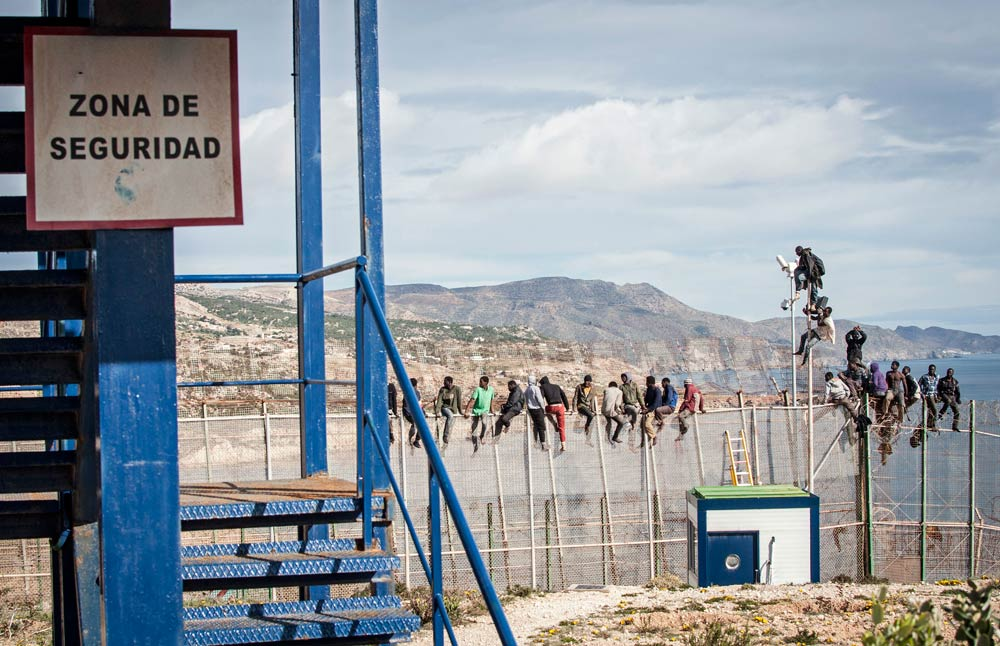 African migrants sit on top of a border fence between Morocco and Spain's north African enclave of Melilla during their latest attempt to cross into Spanish territory, on April 3 2014. (Pic: Reuters)