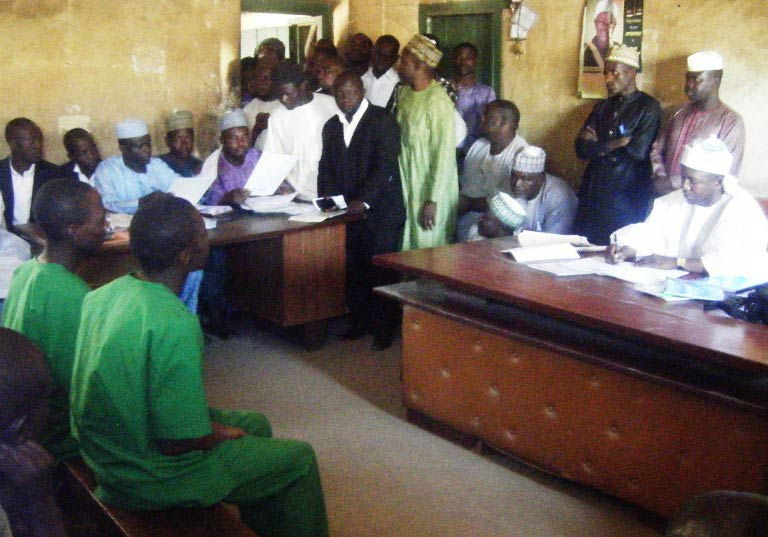 A picture taken on January 22 2014 shows two suspected homosexuals in green prison uniforms (L) sitting before Judge El-Yakubu Aliyu during court proceedings at Unguwar Jaki Upper Sharia Court in the northern Nigerian city of Bauchi. (Pic: AFP)