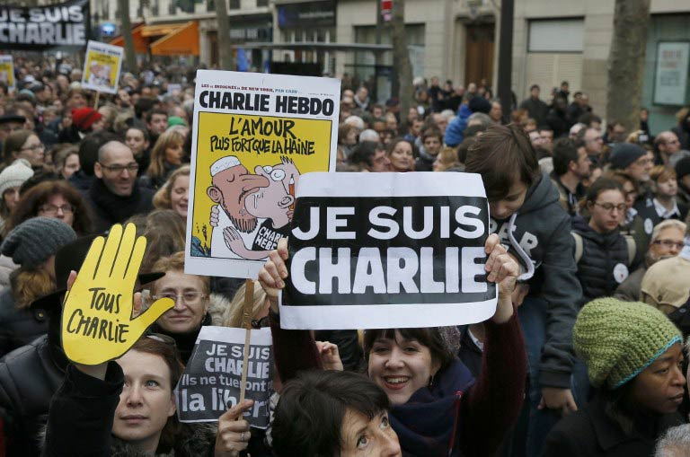 "People wave posters featuring Charlie Hebdo cartoons, ""Je suis Charlie (I am Charlie)"" and ""All Charlie"" in a Unity rally in Paris on January 11. (Pic: AFP)"