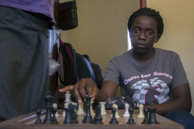 Phiona Mutesi plays a game of chess with her colleagues at the chess academy in Kibuye, Kampala. (Pic: AFP)