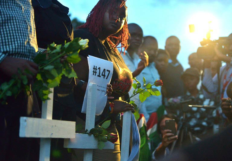 People hold roses and wooden crosses at freedom corner in Uhuru Park during a candlelight vigil in Nairobi on the final day of mourning for the 148 people killed on April 2 by Somalia's al-Shabab Islamists. (Pic: AFP)