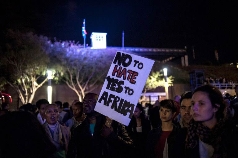 A man holds a placard as he and others attend a silent vigil against xenophobia, held at Constitution Hill in Johannesburg on April 21 2015. (Pic: AFP)