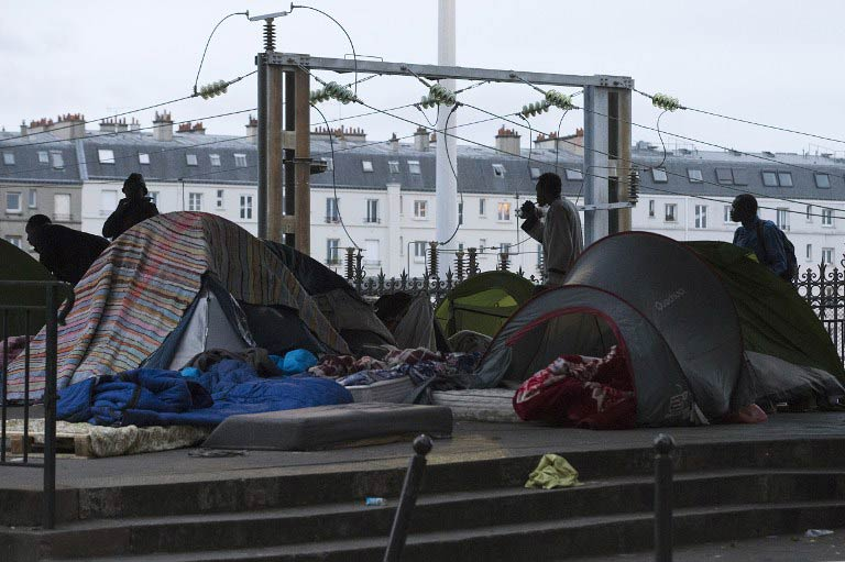 African migrants stand in a camp under a subway bridge in northern Paris before being evicted by French police on June 2, 2015. More than 350 refugees, most of them from Sudan, but also from Eritrea, Somalia and Egypt, have been living in the makeshift camp below the metro tracks between the stations of La Chapelle and Barbes-Rochechouart in the north of the French capital. (Pic: AFP)