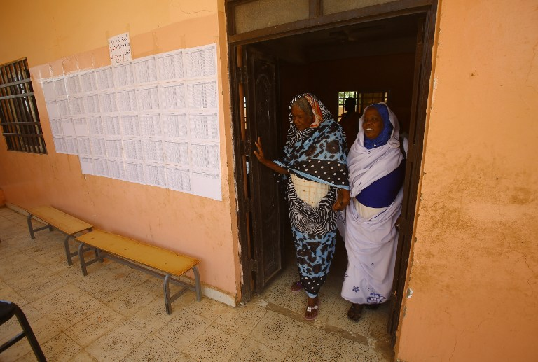 Sudanese women leave after voting at a school turned into a polling station in Al-Jarif West, outside Khartoum, Sudan. Pic: Ashraf Shazly/AFP