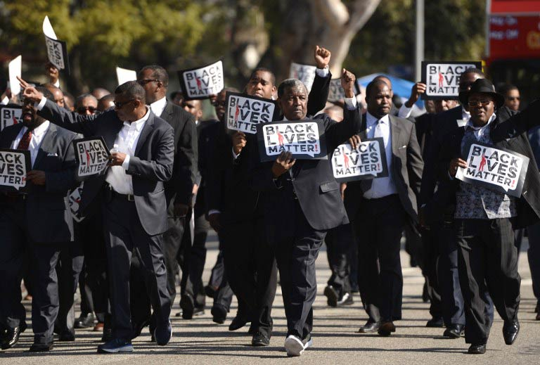 "Men holding signs reading ""Black Lives Matter"" march in the 30th annual Kingdom Day Parade in honor of Dr. Martin Luther King Jr. on  January 19 2015 in Los Angeles. (Pic: AFP)"
