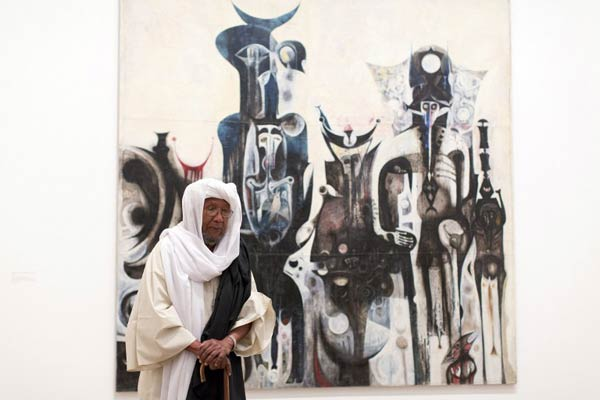 "Sudanese artist Ibrahim El-Salahi poses for a photograph in front of his painting entitled ""Reborn Sounds of Childhood Dreams"" at the Tate Modern in London on July 1 2013. (AFP)"