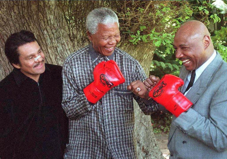 """Nelson Mandela (C) pretends to fight former US world middleweight champion Marvin Hagler (R) in Cape Town on November 12 1997 while former five-time world champion Roberto """"Hands of Stone"""" Duran (L) of the US looks on. (AFP)"""