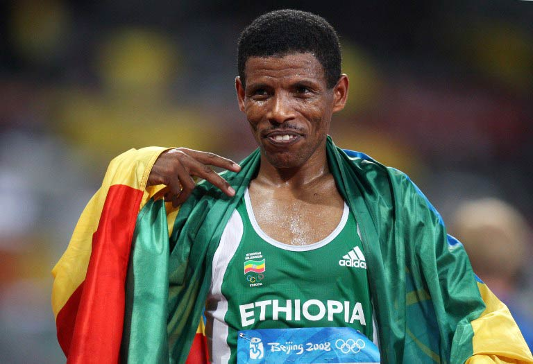 """Haile Gebrselassie celebrating with his national flag after competing in the men's 10 000m final at the """"Bird's Nest"""" National Stadium during the 2008 Beijing Olympics. (AFP)"""